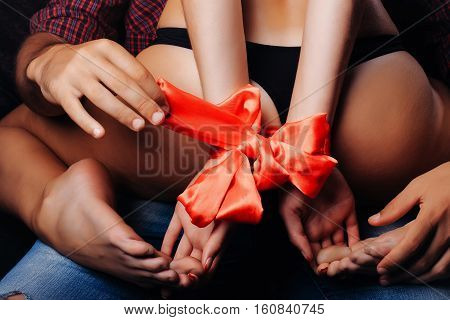 man holding female sexy buttocks of young woman with slim body and legs with bare back in lingerie has red ribbon bow on hands