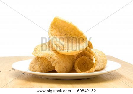 Pile of crunchy prawn cracker in a white plate on a wooden board on white background