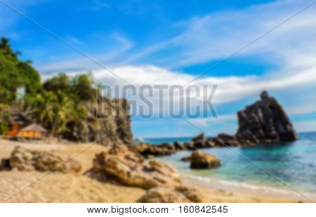 Tropical beach with stones and rocks. Idyllic place by the sea blurry background. Colorful seaside backdrop image. Perfect weather sand beach and sea. Summer vacation on island concept photo in blur
