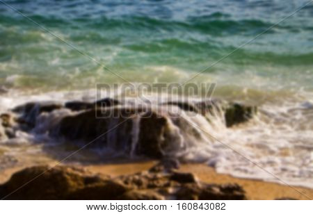 Blue and green sea water and stone beach. Tropical seaside blurry background. Seawater perspective landscape with wave and ripples. Summer travel seaside photo in blur. Sunny day on beach blurred card