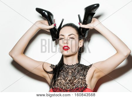 Pretty girl young beautiful fashion brunette woman female model poses with elegant high heel black shoes on head isolated on white