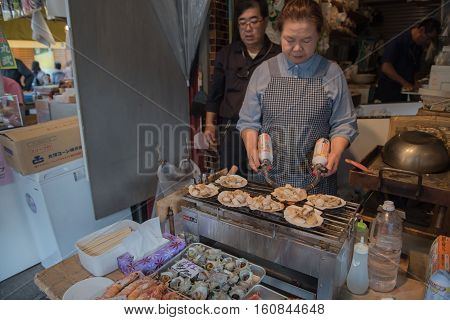 TOKYO  , JAPAN - MAY 2 , 2016 :  Chefs are cooking grilled shell at Tsukiji market.
