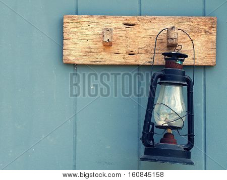 Burning kerosene lamp hang on the wooden wall. Home decoration by old lamp in vinage style.