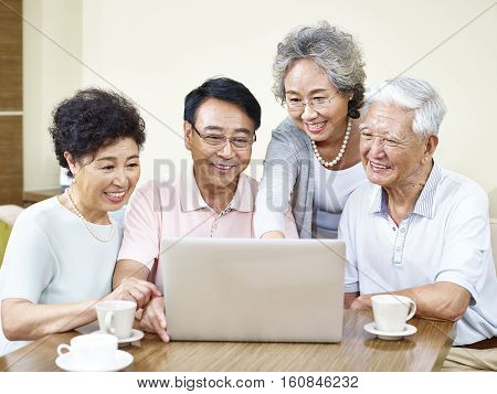 four senior asian people gathering at home using laptop computer together.