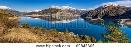 Panoramic view from hiking trail of Serre Poncon Lake in Winter with snow covered mountains. Le Rousset Hautes Alpes Southern French Alps France