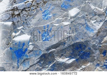 Blue hand prints on cracked metallic shining stone wall