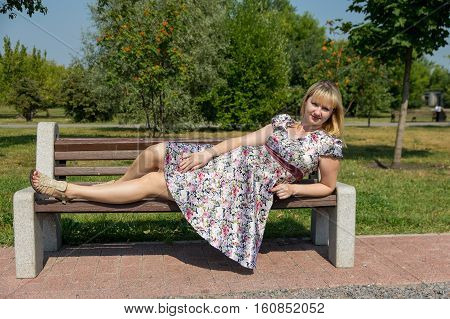 Pregnant woman lies on a wooden bench in the Park