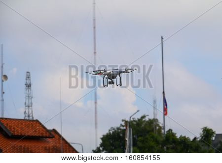 white drone motion hovering in blue sky