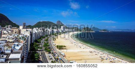 Aerial view of the Copacabana Beach, Forte Duque de Caxias, Sugarloaf Mountain, deep green and blue Atlantic Ocean and deep blue sky, Rio de Janeiro, Brazil