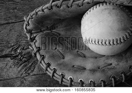 A top view image of an old used baseball and leather baseball glove.