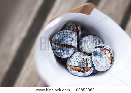 Roasted chestnuts on rustic wooden table in white paper bag with copy space