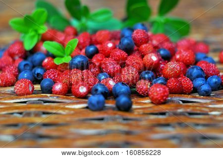 Wild strawberry and bilberry on rattan table