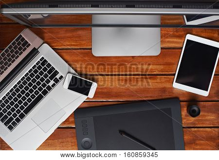 top view on retoucher gadgets on wooden table with laptop, tablet and empty space