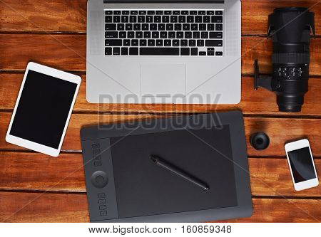 wooden desk of stock photographer with laptop, camera big lens,smartphone and tablet