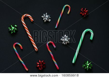 Pattern of Christmas candy cane and bows for gifts green, red and silver colors. New Year decorations  Black background, top view, flat lay