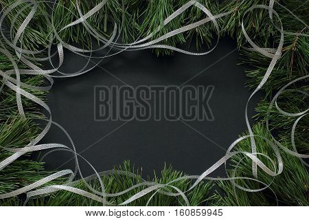 Frame of pine branches decorated with silver ribbon. Christmas/New Year decorations  Black background, top view, flat lay, copy space