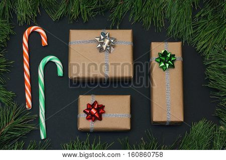The composition of the three gifts wrapped in kraft paper and two candy canes. Frame of pine branches. Christmas/New Year decorations Black background, top view, flat lay, copy space