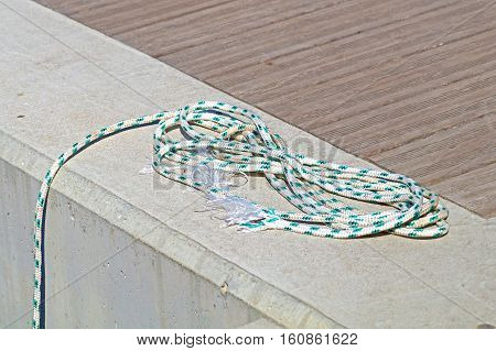 Coiled mooring line tied around cleat on a wooden dock