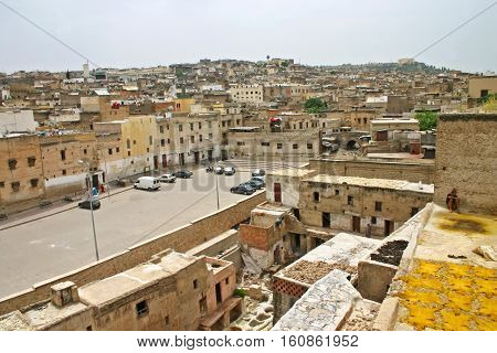 FEZ MOROCCO - MAY 19 2006: City skyline and view of rooftops drying hides and dye pots at leather tanneries at the Terrace de Tanneurs in the ancient medina Fes el Bali in Fez Morocco.