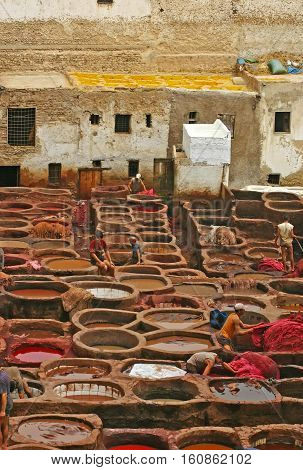 FEZ MOROCCO - MAY 19 2006: View of tanners working in the dye pots at leather tanneries from the Terrace de Tanneurs in the ancient medina Fes el Bali in Fez Morocco.