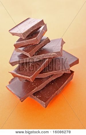 Stack Of Dark Chocolate Pieces,  Over Orange Background