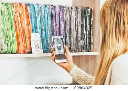 Woman shopping scanning qr code with smartphone on showcase sale advertising modern technology and fashion retail concept
