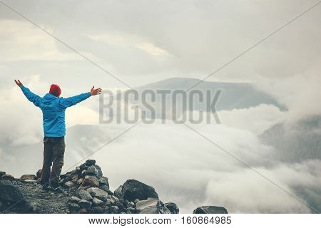 Traveler Man hands raised on cliff hiking enjoy cloudy foggy mountains landscape Travel Lifestyle freedom concept adventure vacations outdoor