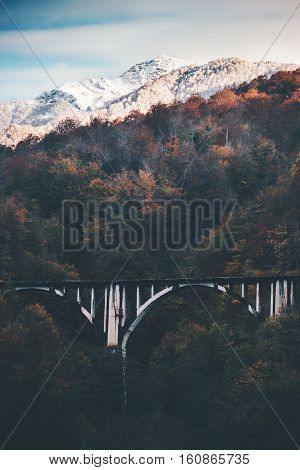 Railway Bridge and snowy Mountains Landscape with autumn forest Travel scenery epic view