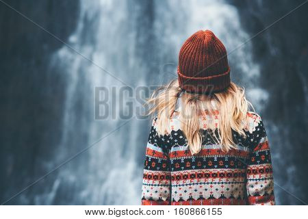 Woman and waterfall Travel Lifestyle adventure concept vacations into the wild wearing cozy sweater and hat