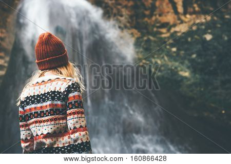 Woman enjoying waterfall Travel Lifestyle adventure concept active vacations into the wild wearing cozy sweater and hat rear view