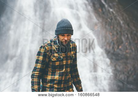 Bearded Man walking with waterfall on background Travel Lifestyle adventure concept vacations into the wild wearing cozy shirt and hat lumberjack style