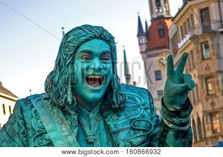 Munich, Germany - April 13, 2013: Street mime actor at Marienplatz in Munich, earns money as a copper statue. Blue-green color symbolizes the copper oxides. The actor welcomes the audience.