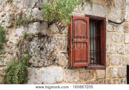 A rustic window with wooden shutter on the outside of a Lebanese house.