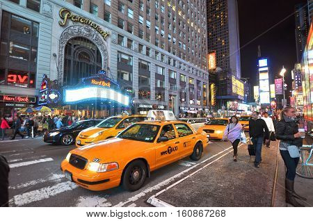 NEW YORK CITY - OCT. 2, 2011: Times Square and yellow cab on Broadway at night wide angle, Manhattan in New York City, USA.
