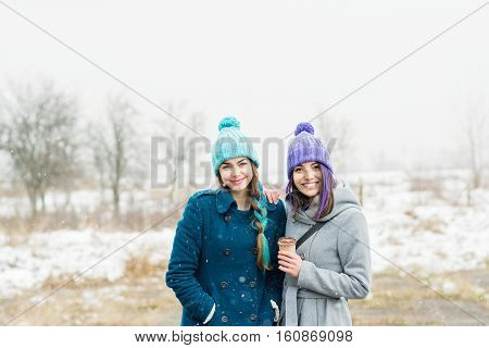 Outdoors portrait of two teenage female friends in winter, wearing modern colorful coats and  knit beanie hats. Natural light, mild retouch.