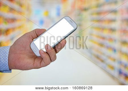 Man Checking Shopping List On Her Smartphone At Supermarket.