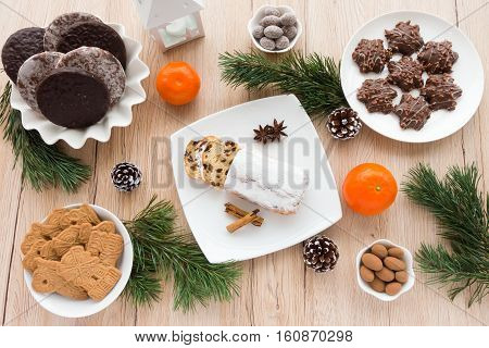 Arrangement of Gingerbread Spiced Biscuits and Mini Christstollen on light wooden background surrounded by Christmas decoration.