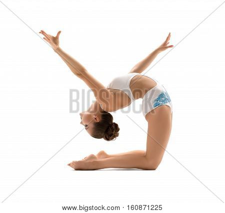 Beautiful female gymnast doing acrobatic exercise, isolated on white background. Young athletic woman in bright leotard practicing in gymnastics