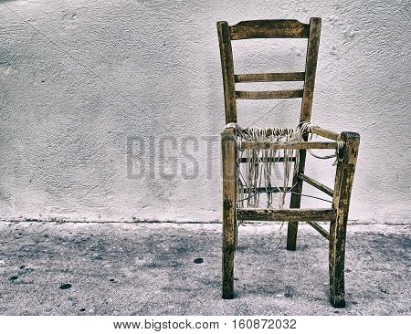 old worn chair on blank wall, heavy instagram filtered