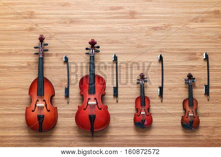 Set of four toy string musical orchestra instruments: violin, cello, contrabass, viola on a wooden background. String Quartet. Music concept. Cello and three violins, all vintage instruments.