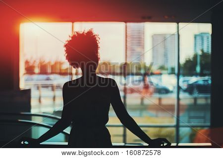 Silhouette of young black curly Brazilian girl in front of window standing in supermarket with blurred escalator behind her and cityscape out of the window Rio de Janeiro Brazil