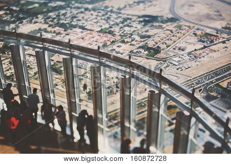 True tilt shift shooting of observation deck of Burj Khalifa skyscraper with group of people observing Dubai from top: highway sand areas residential buildings and streets