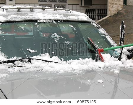 Brushing snow off of a car's windshield after a snow storm.