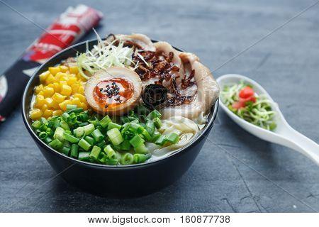 japanese tonkotsu ramen, pork bone broth noodles with chashu pork, egg, corn and scallions