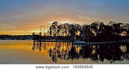 Tranquil Dawn - Orange and gold sunrise over water with skyline tree silhouettes has clear water reflections Photographed at Rathmines Lake Macquarie New South Wales Australia.