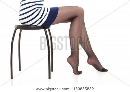 Beauty woman legs in black tights. Part body of slim attractive girl wearing striped dress skirt and pantyhose isolated on white.