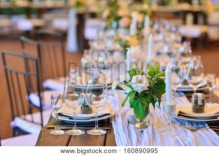 Wedding. Banquet. The chairs and table for guests decorated with candles served with cutlery and crockery and covered with a tablecloth.