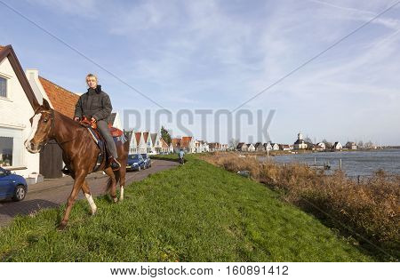 Durgerdam, Netherlands, 22 november 2016: girl on horseback on durgerdam dike near amsterdam in the netherlands