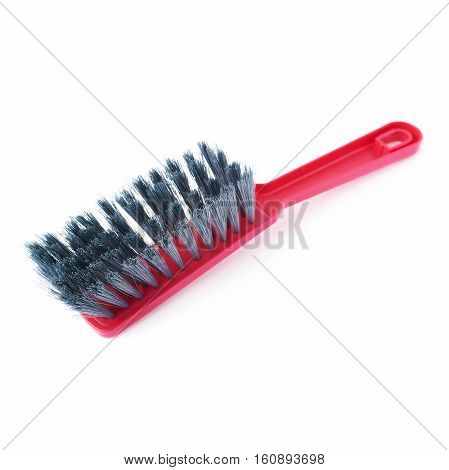 Single red plastic cleaning brush isolated over white background