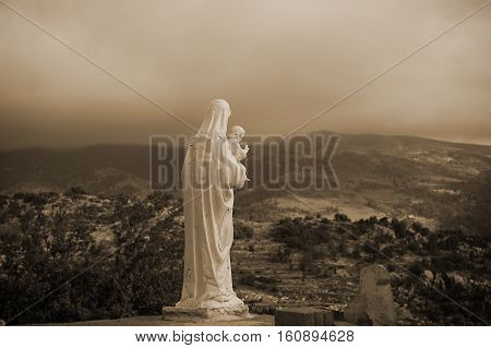 A back view of Virgin Mary holding Baby Jesus overlooking a gloomy setting.